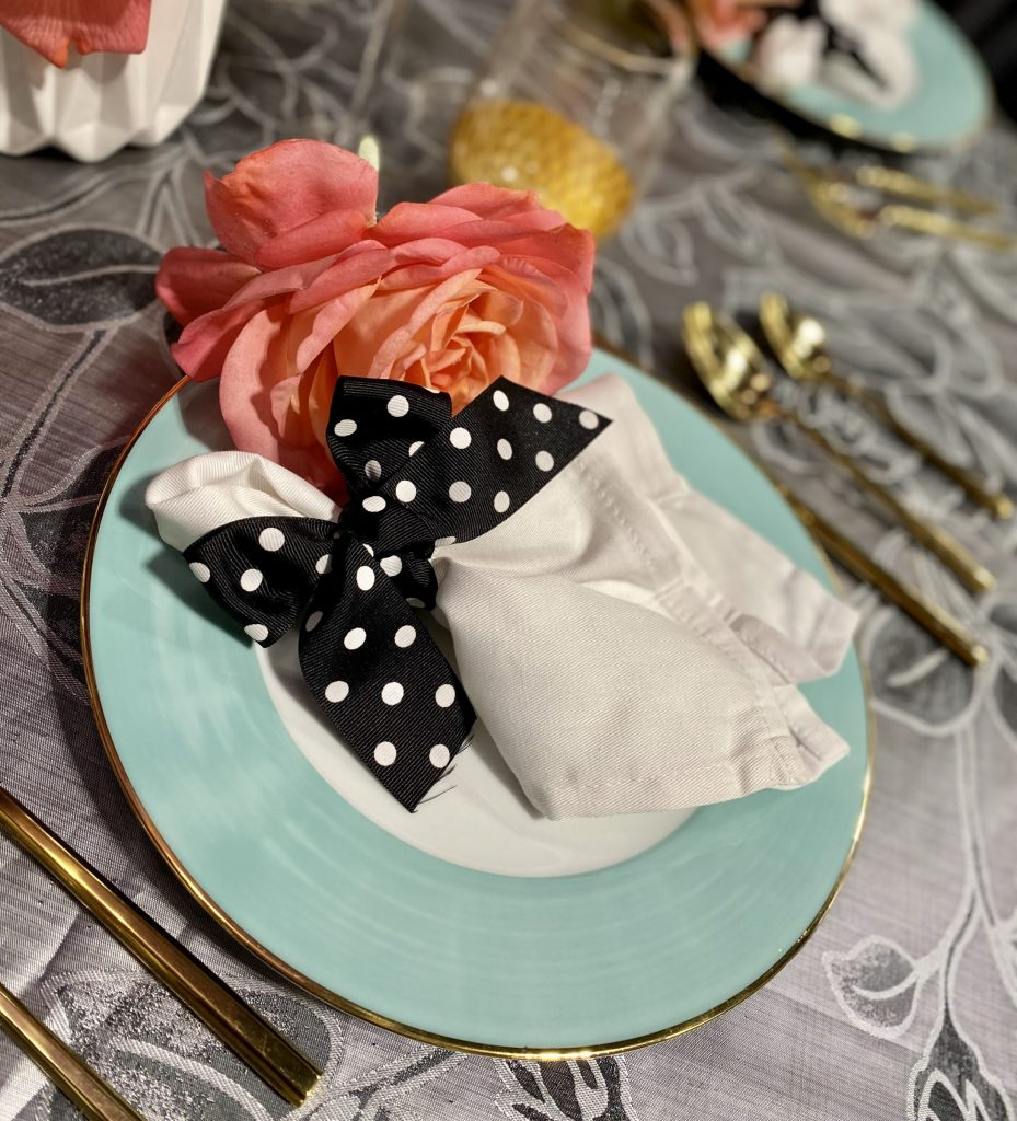 Blue wedding plate with polka dot napkin and pink flower