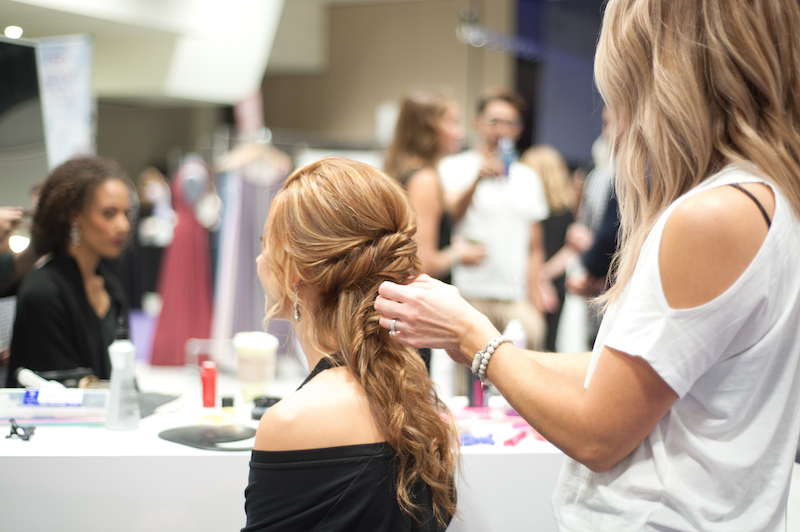 Model gets hair done before Twin Cities Bridal Show