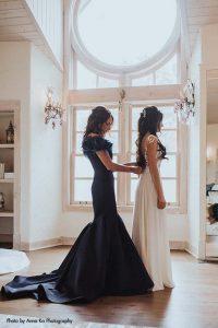 Mother of bride in long navy gown helps bride