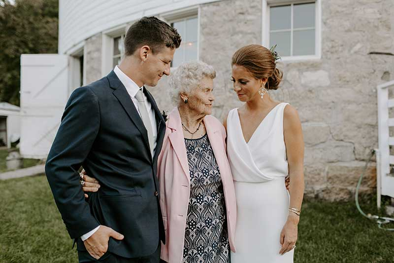 Bride and groom stand with grandmother at wedding