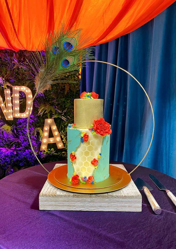 Two-tier blue, gold, and red boho wedding cake by Sweet Lulus