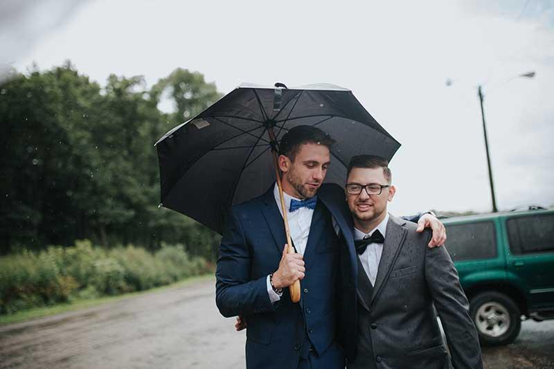Groom and groomsman walk with umbrella after wedding