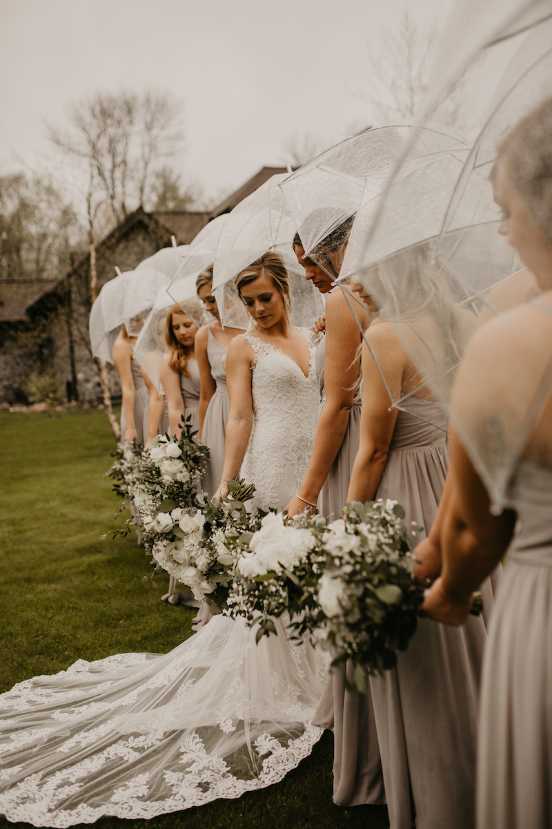 Bride and bridesmaid stand outside with clear umbrellas