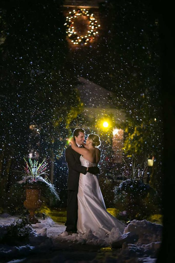 Bride and groom stand as snow falls during unpredictable weather