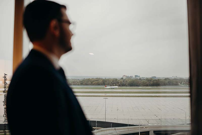 Groom looks out window at airport wedding