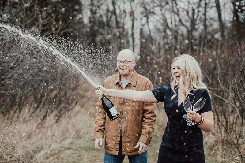 Couple pops champagne at fall photoshoot by Anna Ko Photography