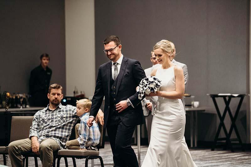 Bride and groom walk down aisle at hotel wedding