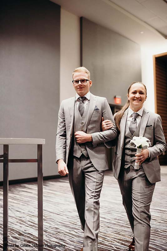 Bridesmaid in gray suit walks down aisle with groomsman