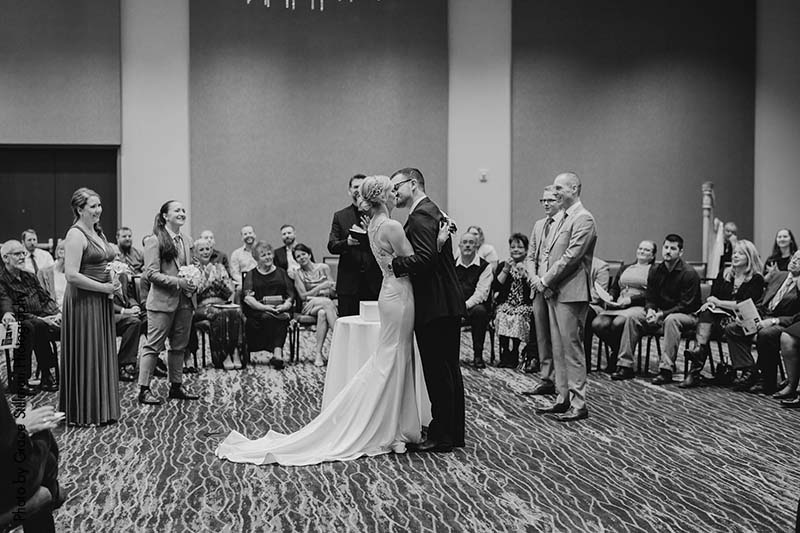 Bride and groom share first kiss at ceremony in luxury hotel ballroom
