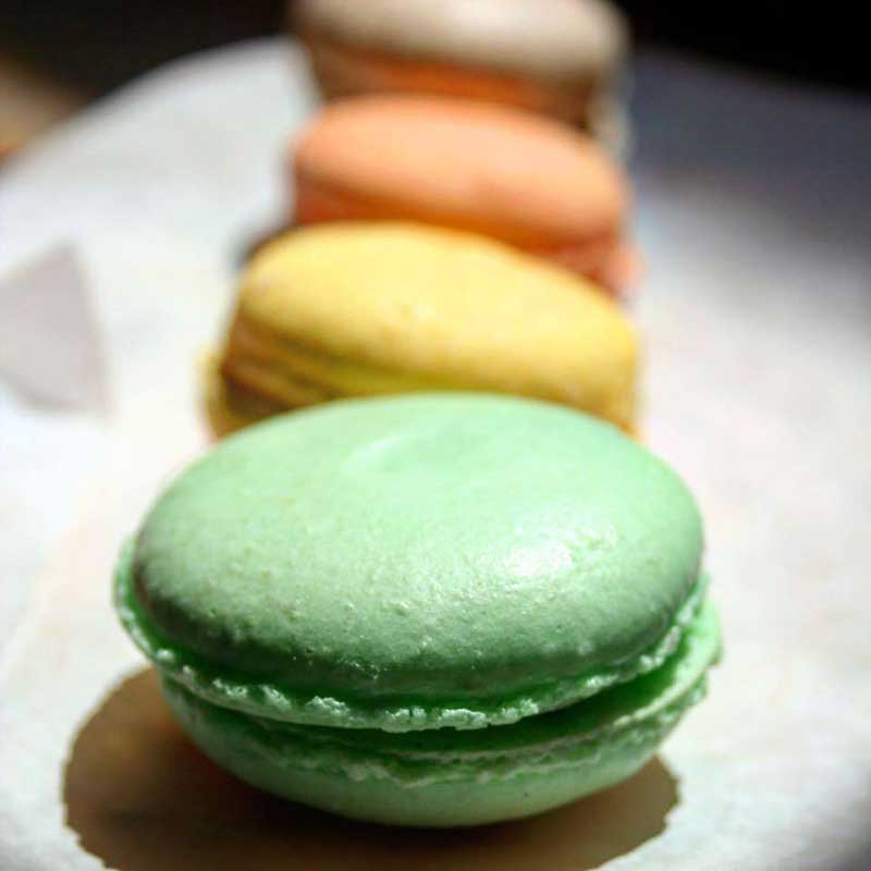 Green, yellow, and orange French Macarons for wedding dessert