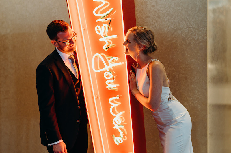 Bride and groom with neon sign at MSP wedding