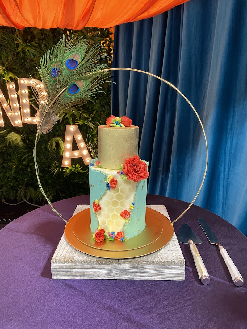 Geometric blue and gold wedding cake with red flowers
