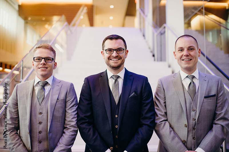 Groomsmen with groom pose for photo in luxury hotel lobby