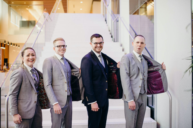 Bridesmaid in gray suit poses with groomsmen