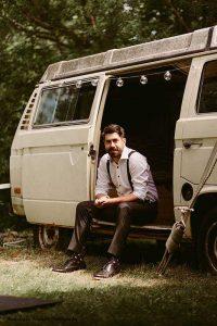 Groom sits in vintage van before wedding
