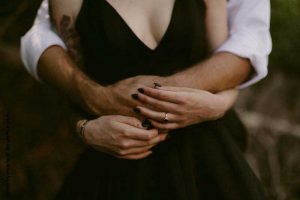 Moody photo of bride and groom holding hands
