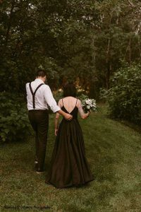 Bride in black dress walks with groom into forest
