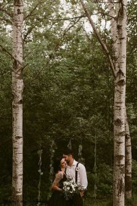 Couple poses in forest with birch trees