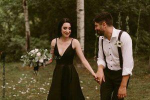 Bride in black wedding dress and groom in suspenders at outdoor wedding