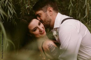 Bride and groom pose with greenery