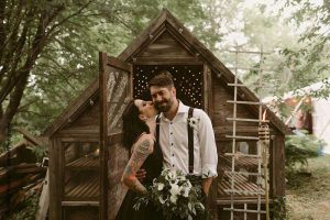 Bride and groom with rustic shed at wedding