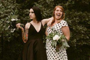 Bride in black dress bridesmaid in polka dot dress