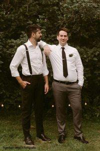 Groom poses with best man at dark wedding