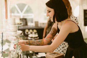 Bride and baker prepares desserts at dark wedding