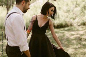 Bride in black wedding dress and groom in suspenders