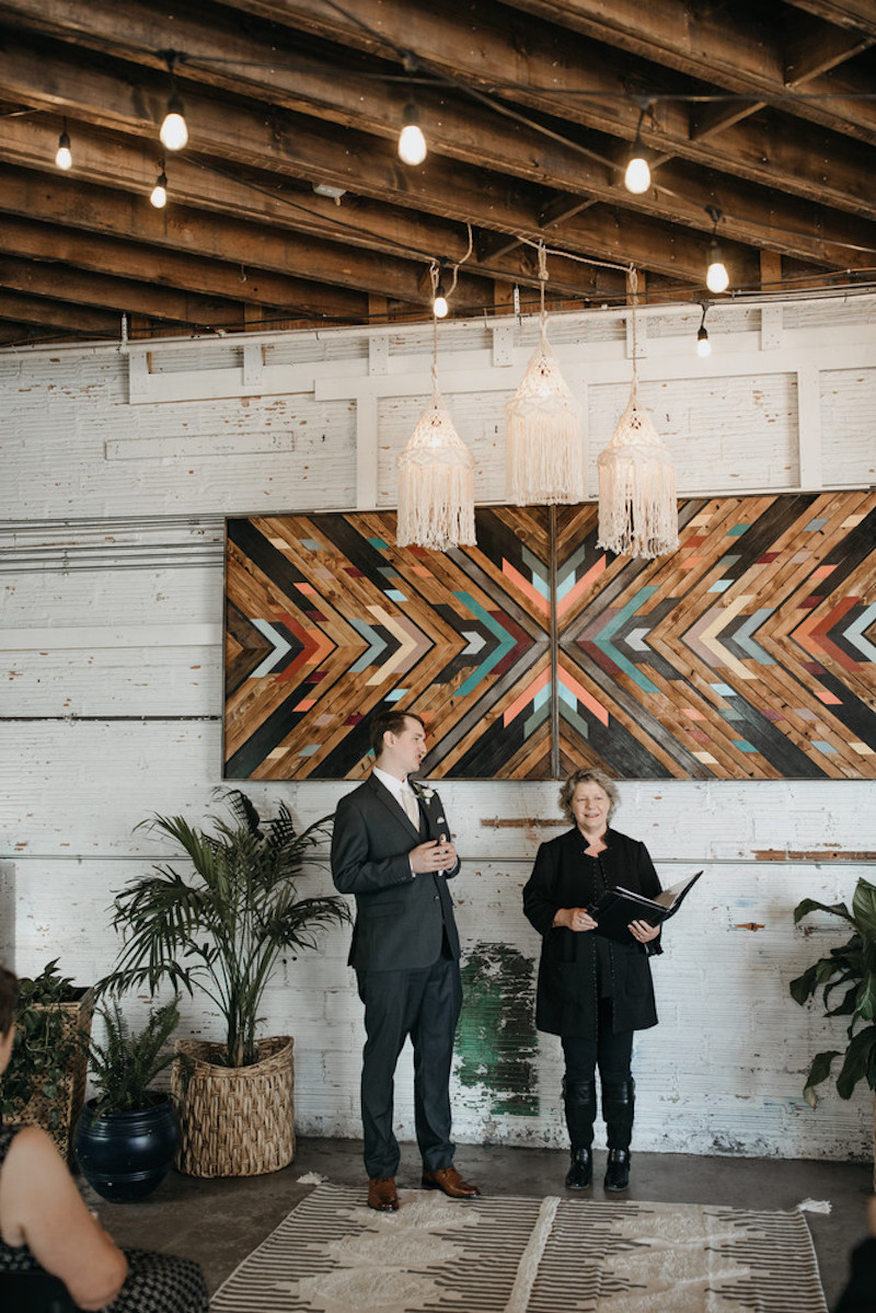 Officiant stands with groom at alter