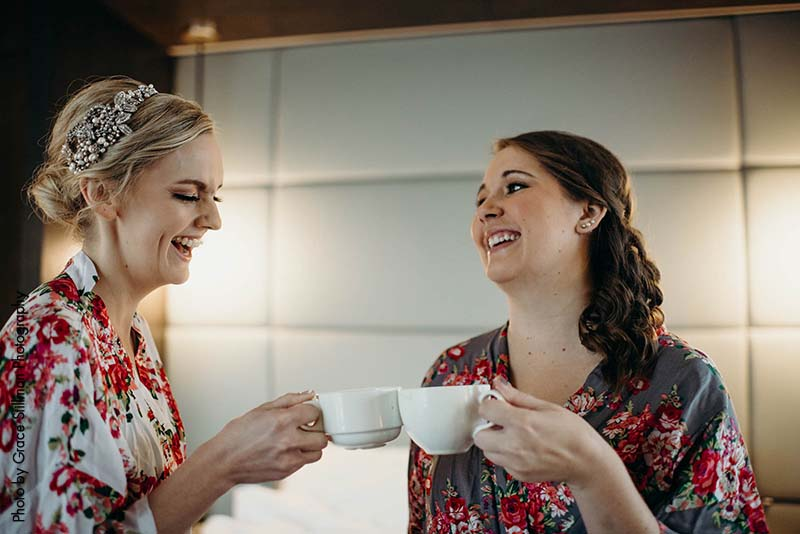 Bride and bridesmaid in floral robes cheers with cup of coffee