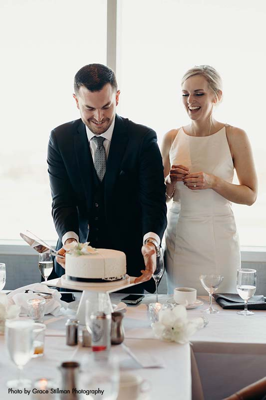 Bride and groom cut cake at hotel daytime wedding