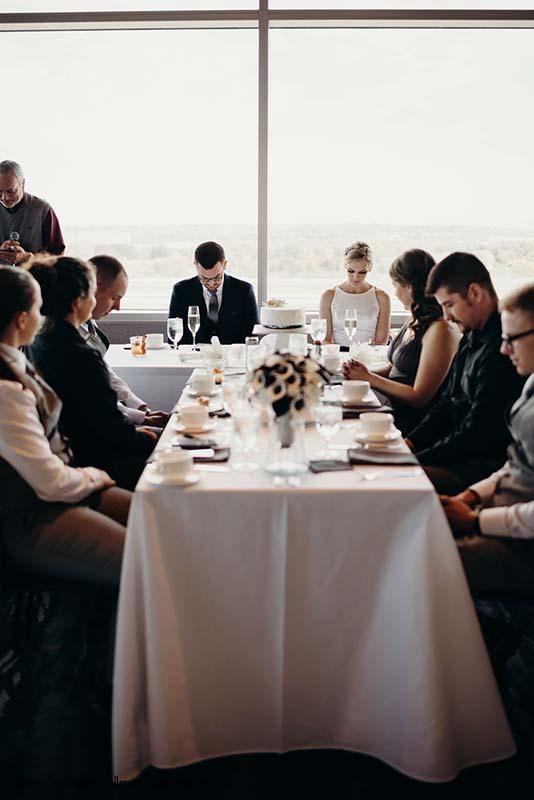 Bride and groom pray before wedding dinner