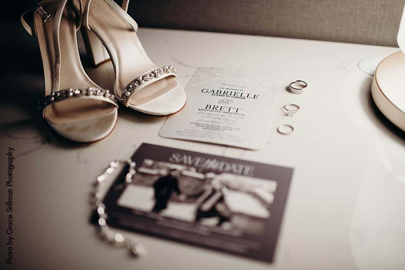 Classic wedding detail shot with shoes, accessories, and invite