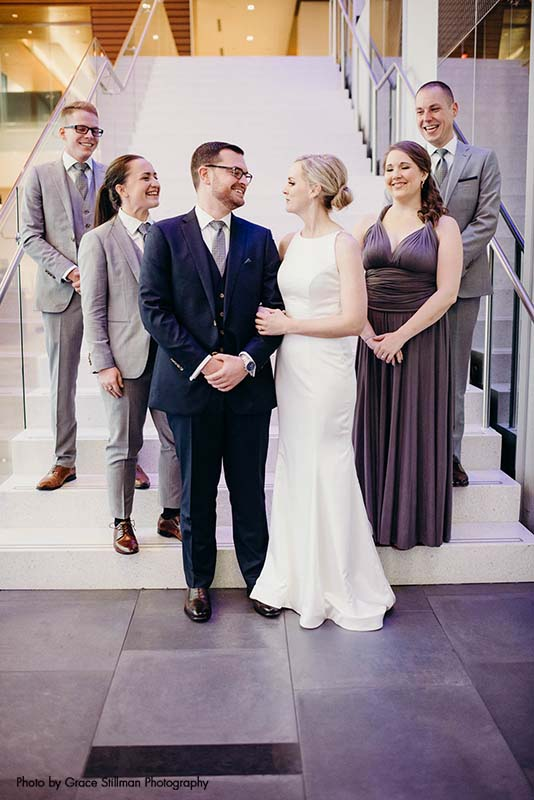 Small wedding party poses for photo on stairs of hotel lobby