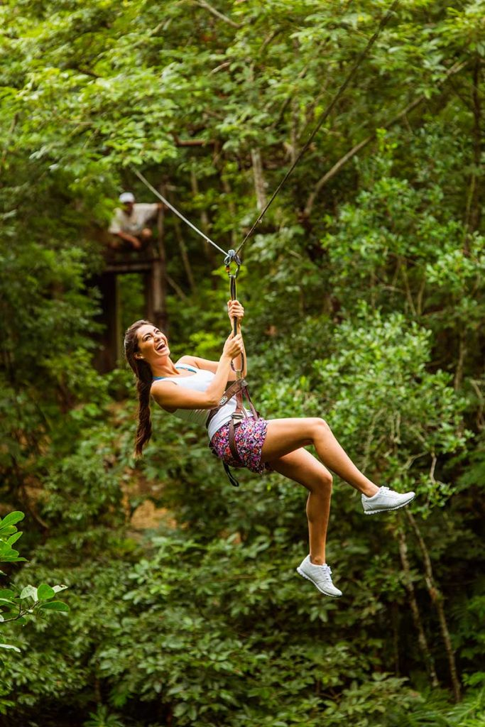 Woman zip lines over Cenote Xcanche in the State of Yucatan