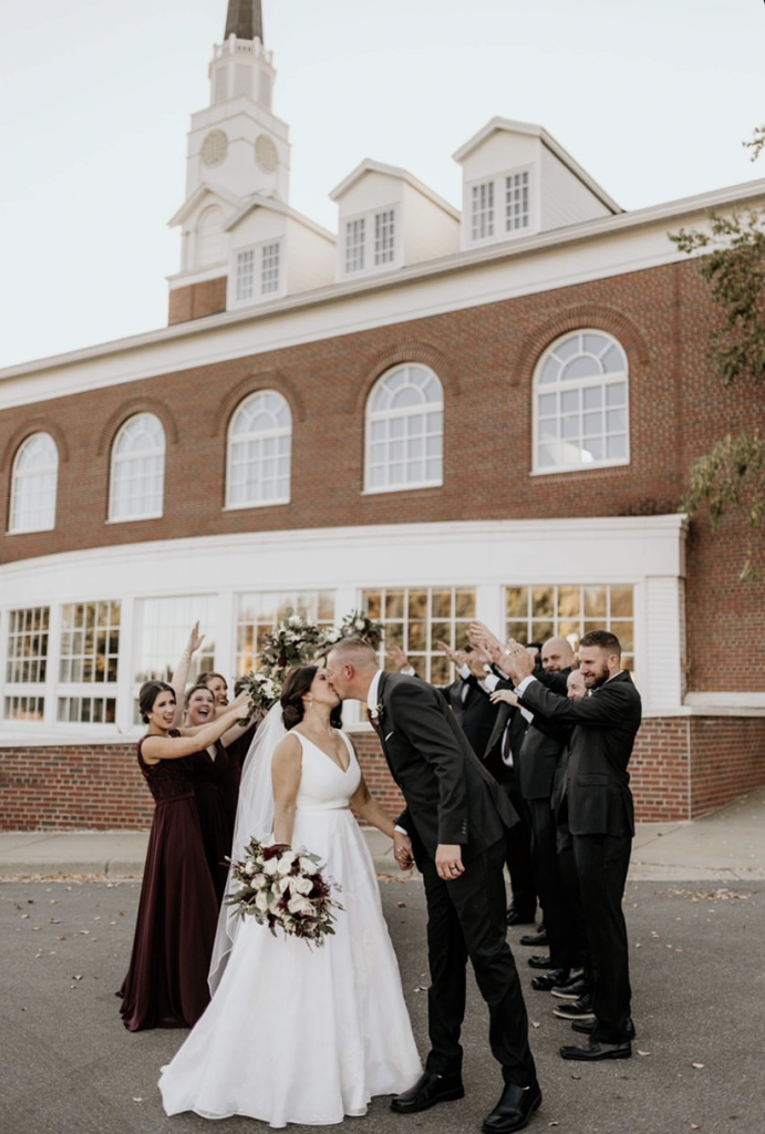Bride and groom kiss and wedding party celebrates behind them
