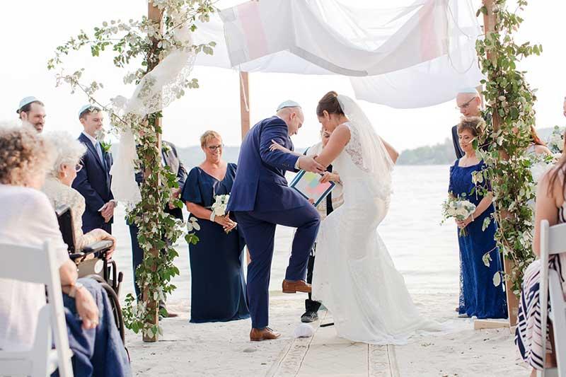 Bride and groom break glass in traditional jewish wedding ceremony