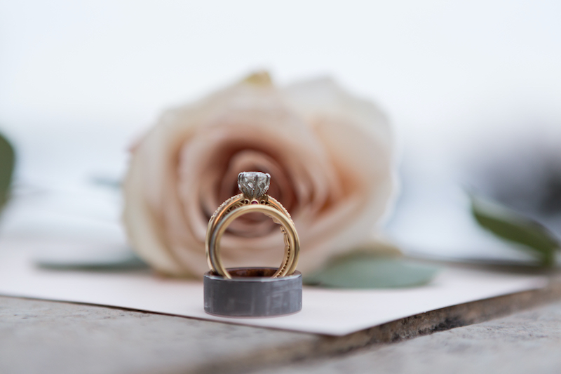 Gold engagement ring and black wedding ring sit in front of pink rose