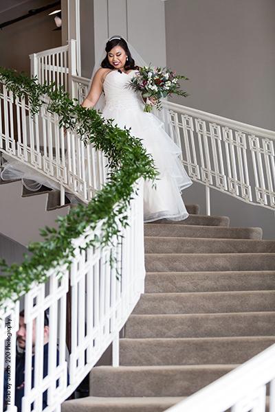 Bride wears ballgown dress as she walks down stairs