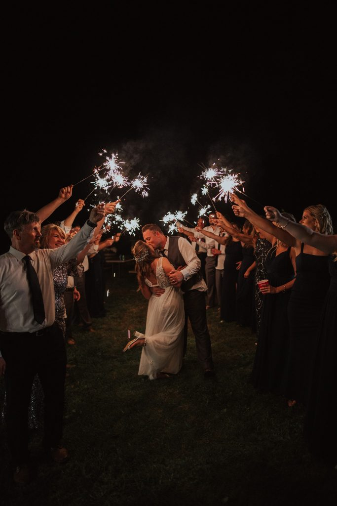 Bride and groom kiss under sparklers