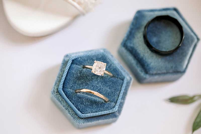 Cushion cut engagement ring shapes on blue velvet ring box