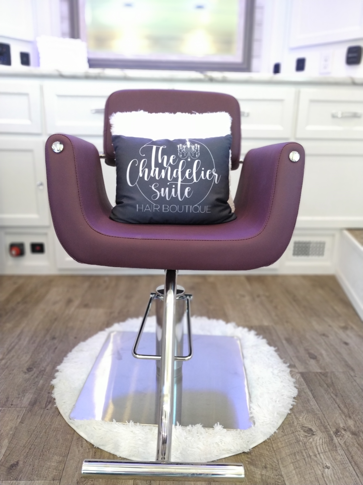 """Purple beauty chair with pillow that says """"The Chandelier Suite"""""""