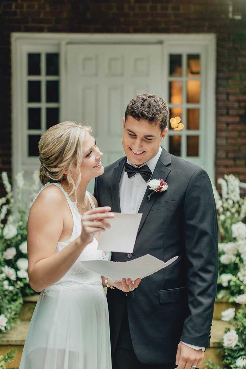 Bride and groom look at wedding invites