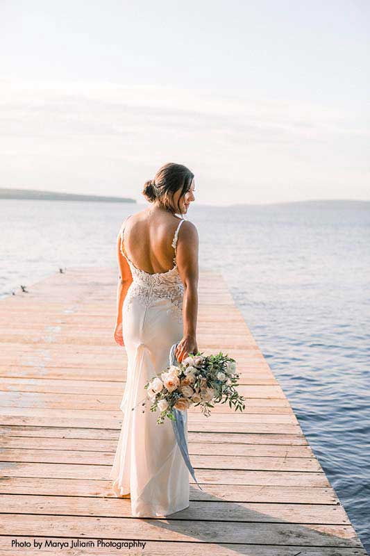 Bride stands on dock by lake