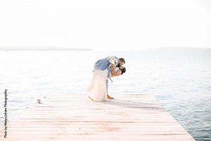 Bride and groom kiss on lakeside dock