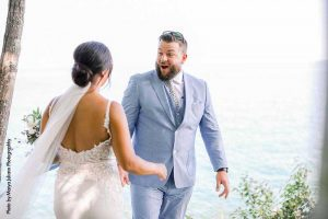 Groom in blue suit sees bride for first time