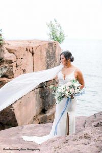 Bride poses for photo outside with long veil