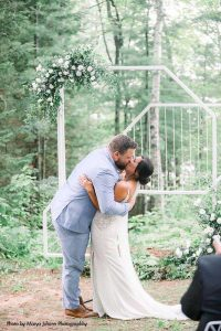 Bride and groom share first kiss at outdoor wedding