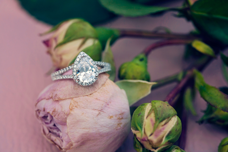 White gold engagement ring on pink flower